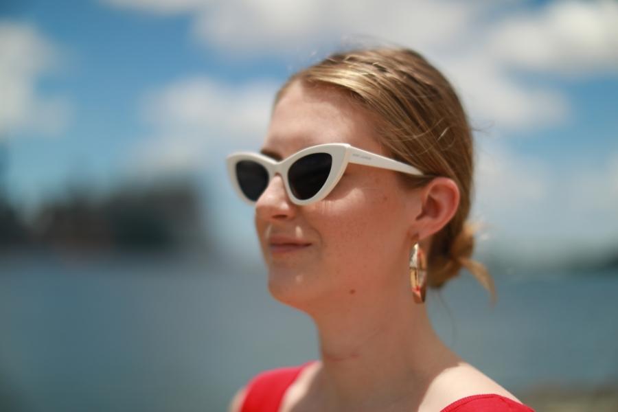 Woman wearing white sunglasses.