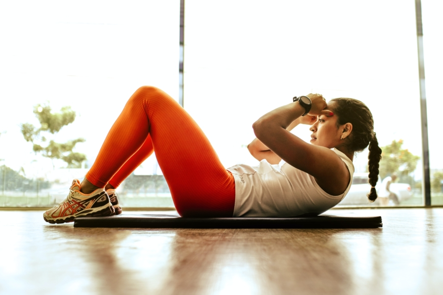 Woman doing sit-ups as part of her exercise routine to keep her high sensitivity c-reactive protein at optimal levels.