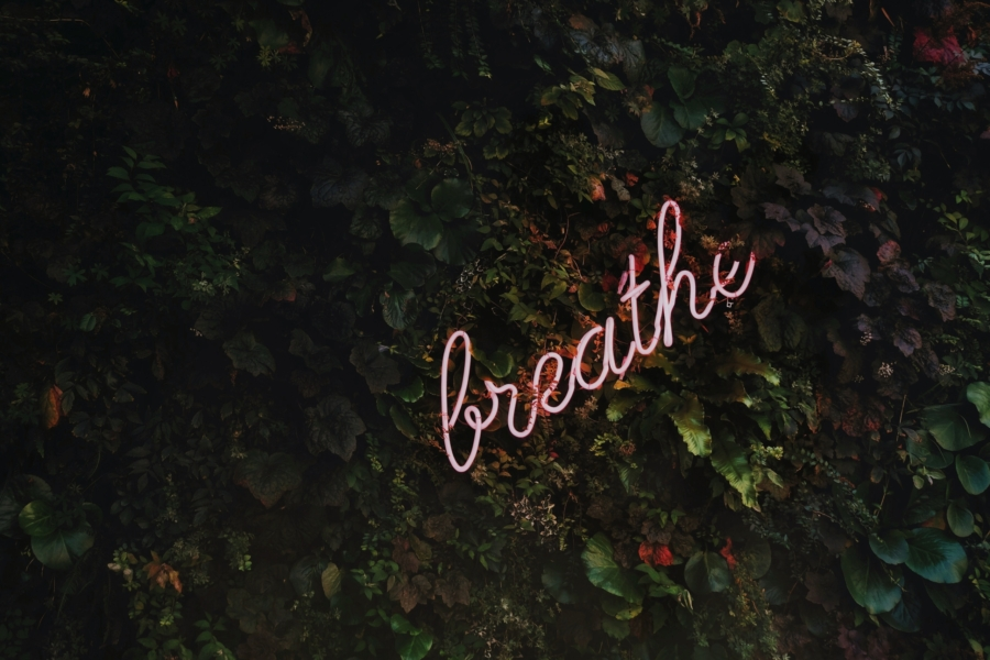 Fluorescent sign reminding us to breathe which is a effect natural anti-anxiety remedy.
