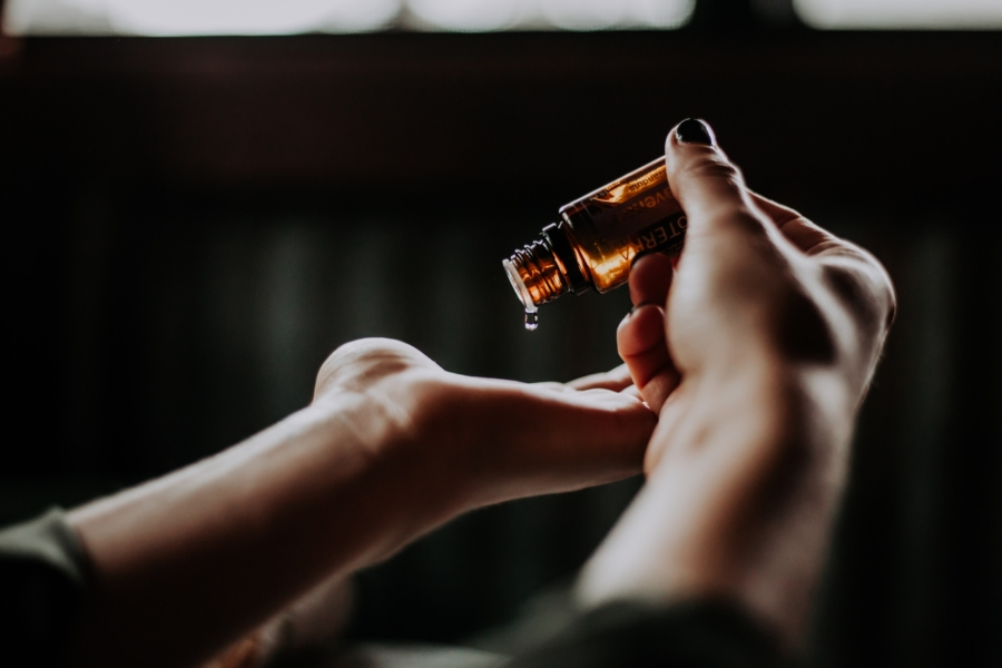 Woman dropping a bliss oil onto her hand in preparation for a transcutaneous acupuncture treatment for depression.