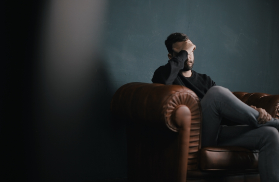 Man sitting in a chair holding his head as he struggles with managing stress and anxiety.