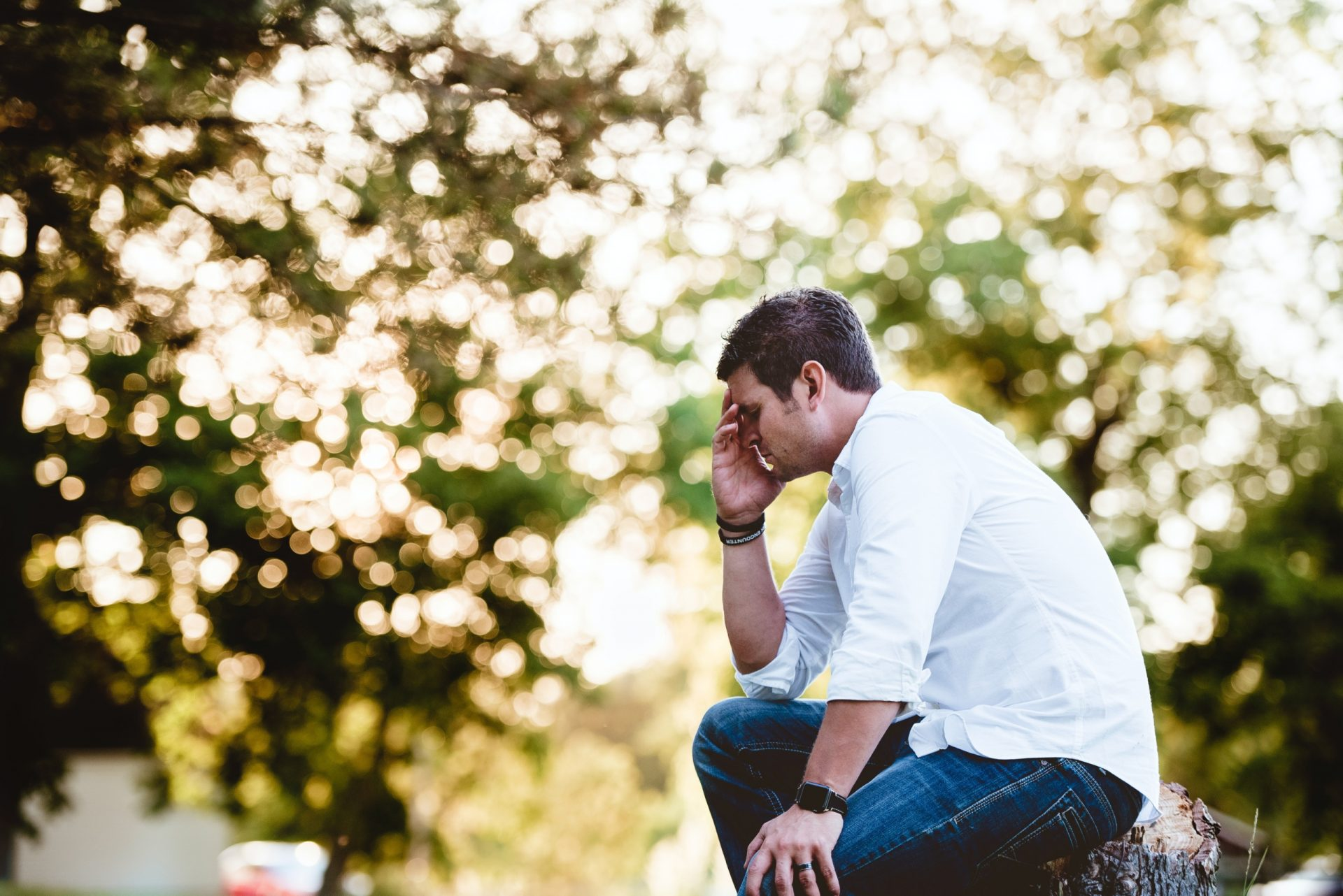 Man sitting on a stump with his head in his hand wondering how to overcome anxiety.