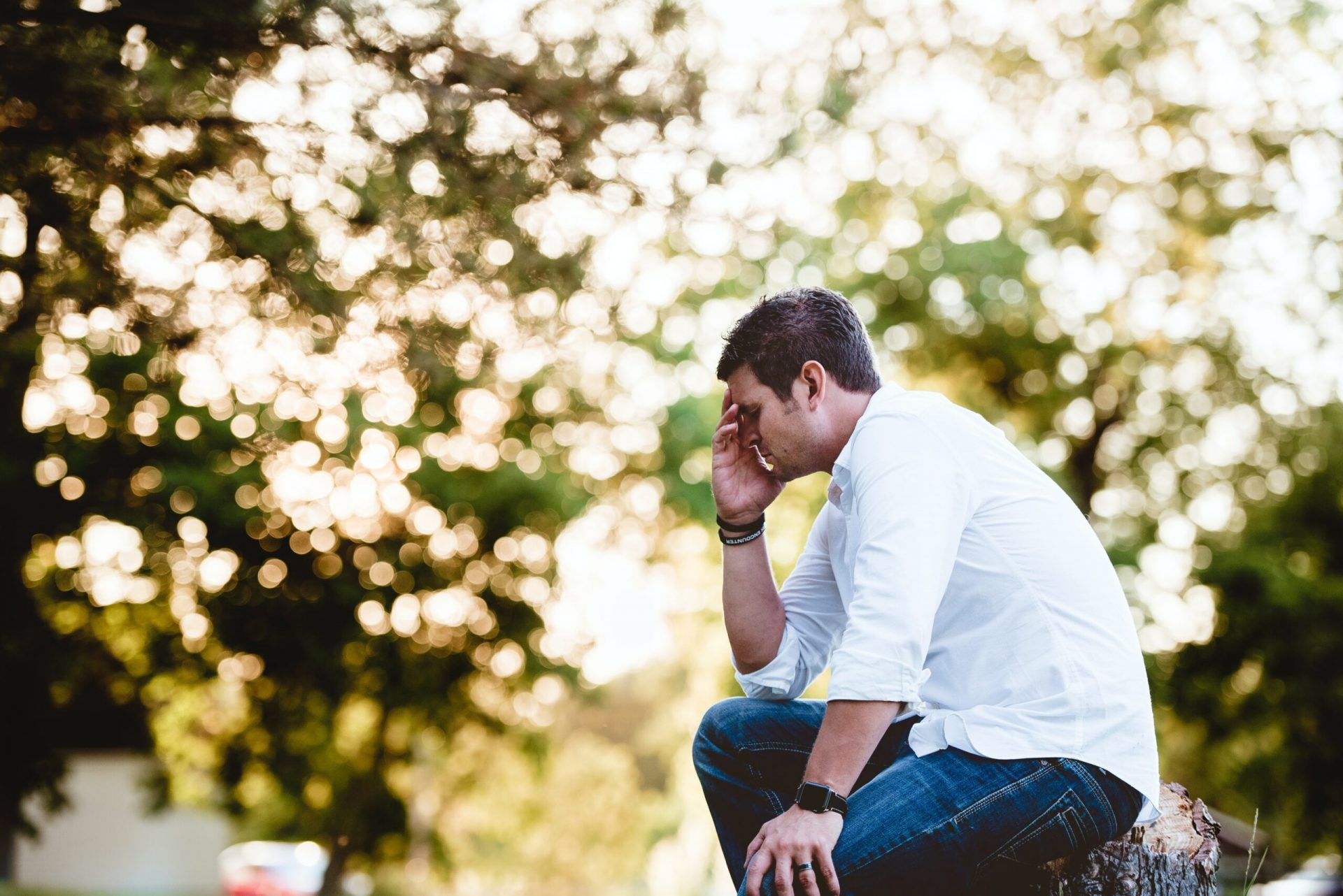 Man sitting on a stump holding his head as he struggles with anxiety, aches and pains everywhere.