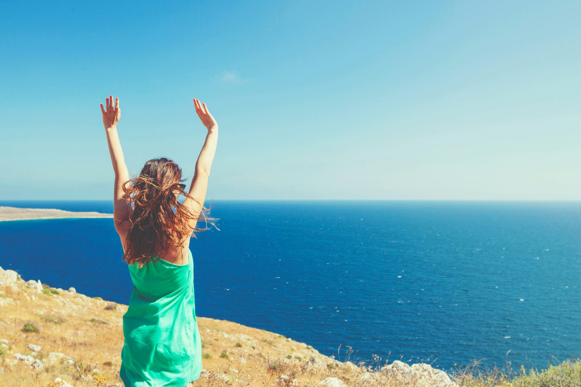 Woman standing on a cliff overlooking the ocean with her hands in the air celebrating being pain-free.