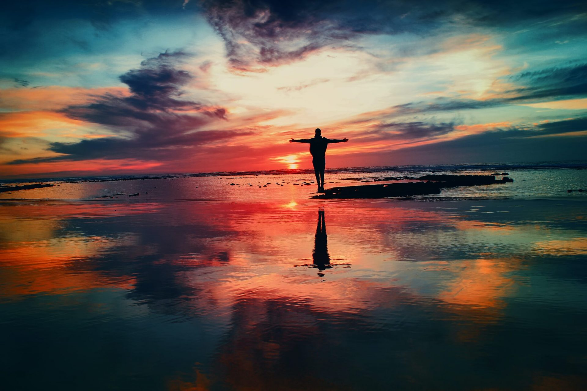 Man standing on the shore with his arms outstretched as he watches the sunrise.