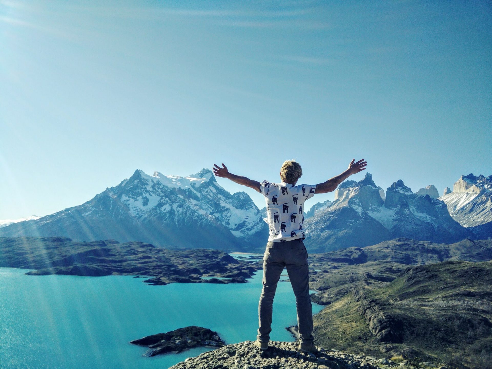 Man standing on top of a mountain with his arms outstretched.
