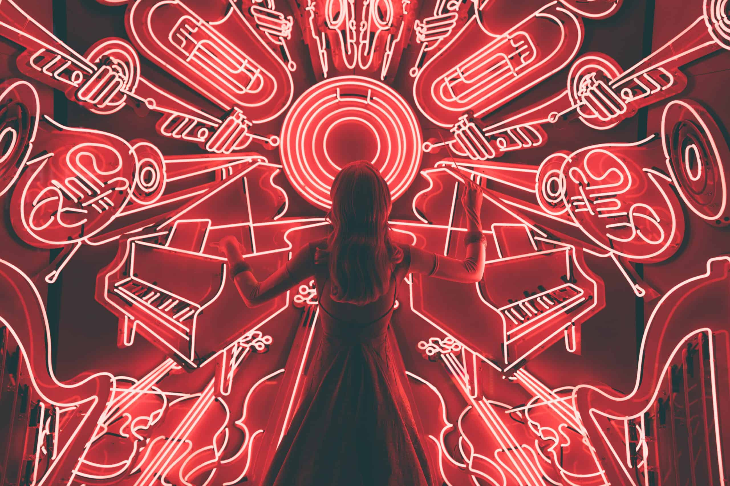 Woman standing in front of neon images of musical instruments pretending to conduct them.