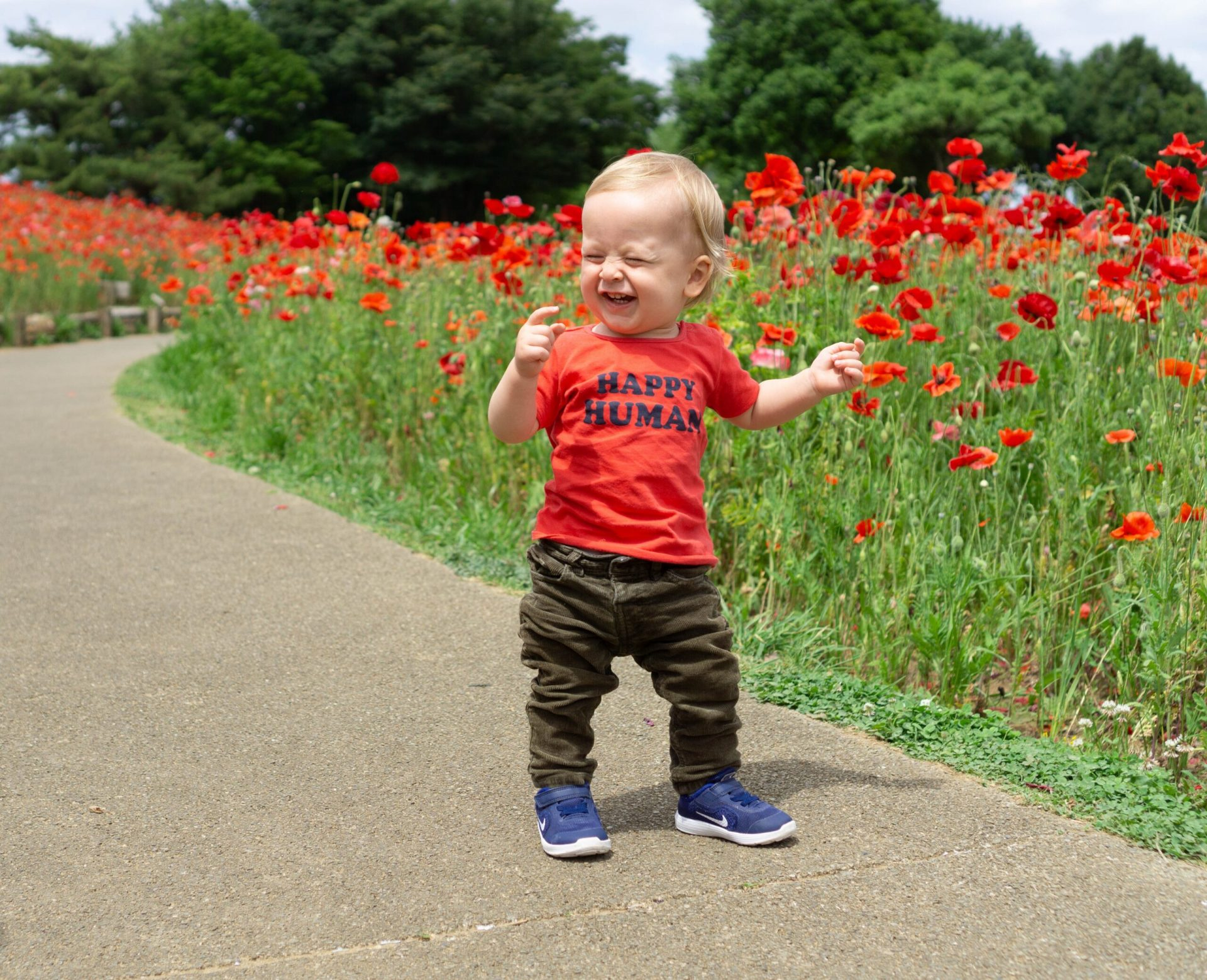 Happy toddler walking on a path next to some flowers.