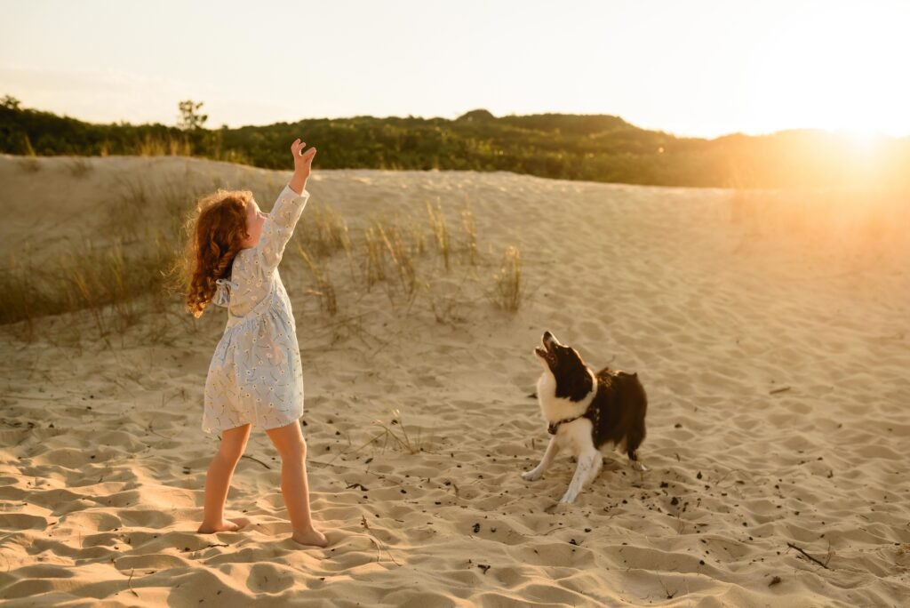 Happy little girl and dog playing together on the beach.