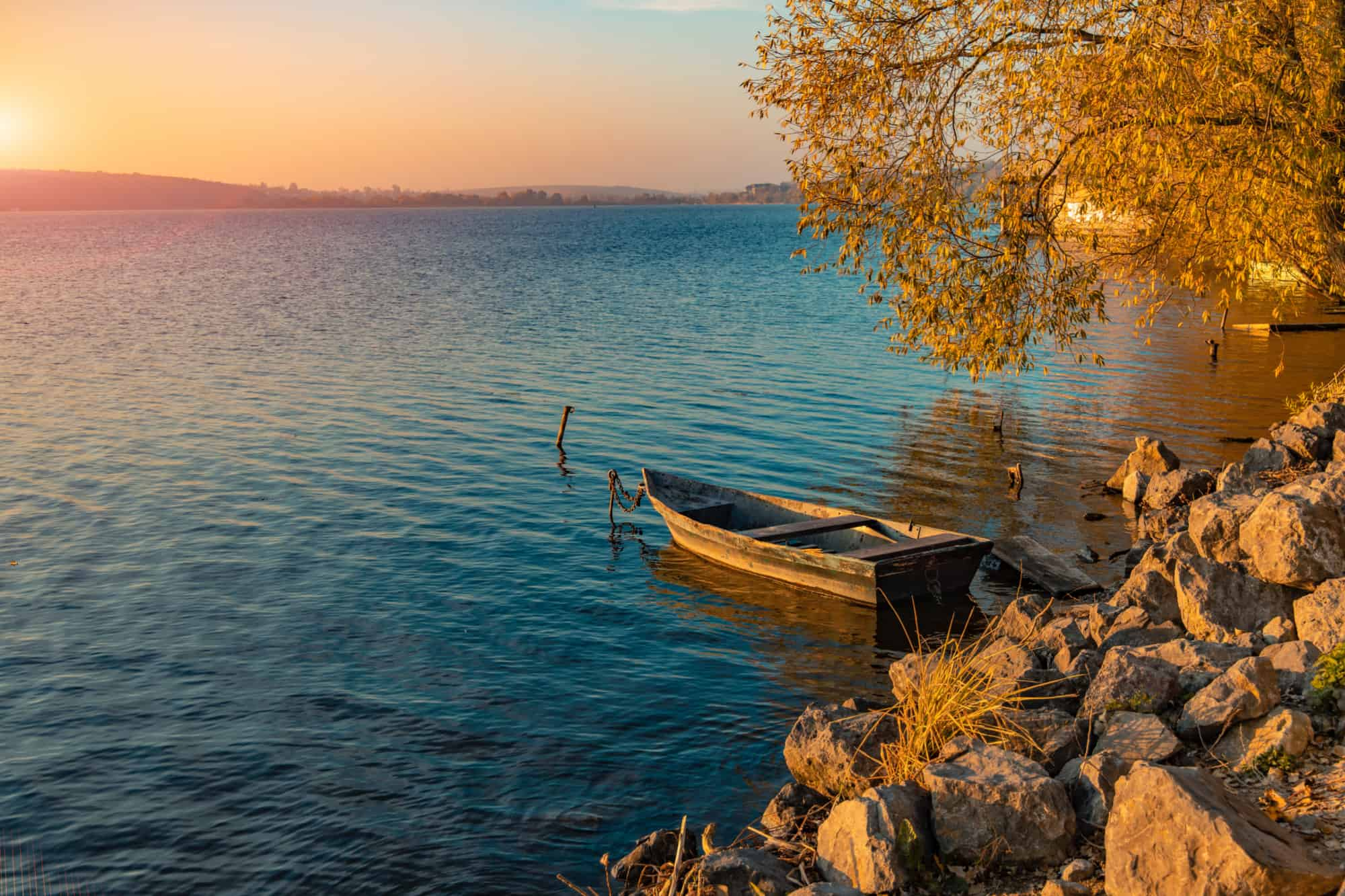 Wooden boat tied to the rocky edge of a lake.