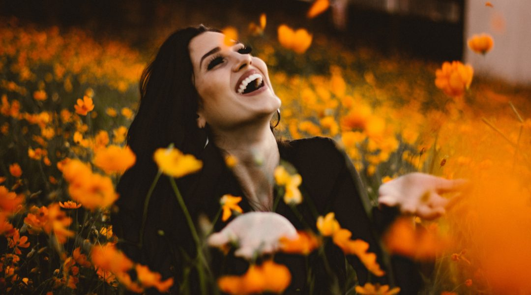 Woman sitting in a field of flowers and smiling.