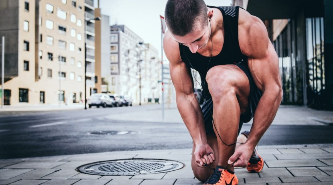 Man tying his shoe as he prepares for a run.