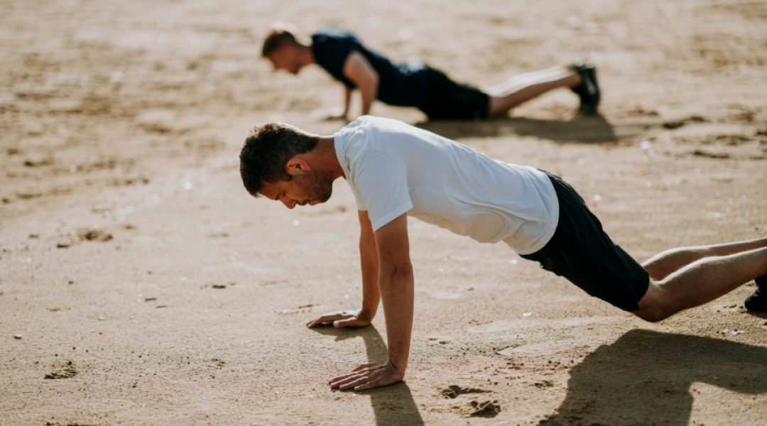 Two men doing pushups on sand in their quest for optimal health and performance.