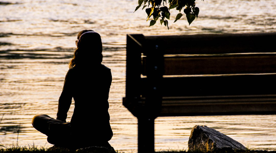 Woman sitting cross-legged on a rock and looking out at placid lake at sunset.