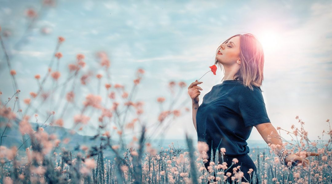 Woman in a field of flowers enjoying a moment in the sun.