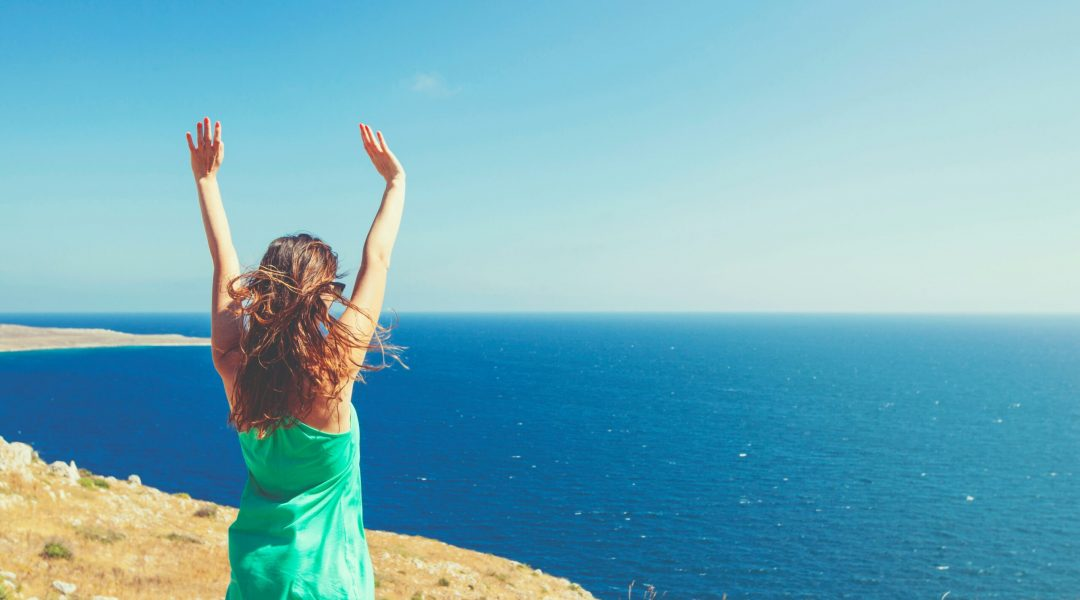 Woman standing on a cliff overlooking the ocean