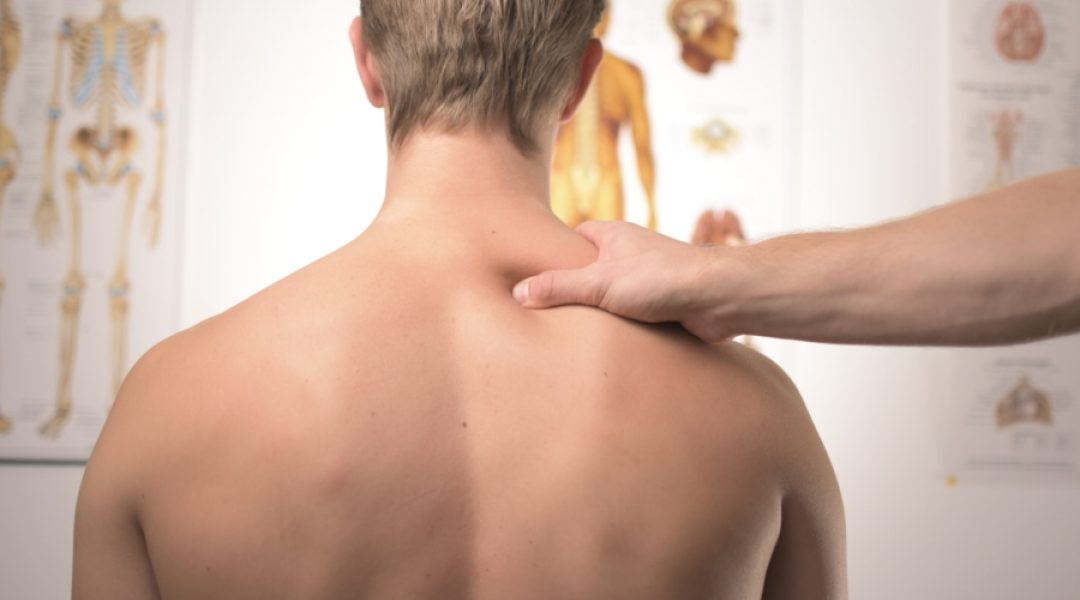 Doctor examining a man's back because he's complaining of chronic arthritis pain.