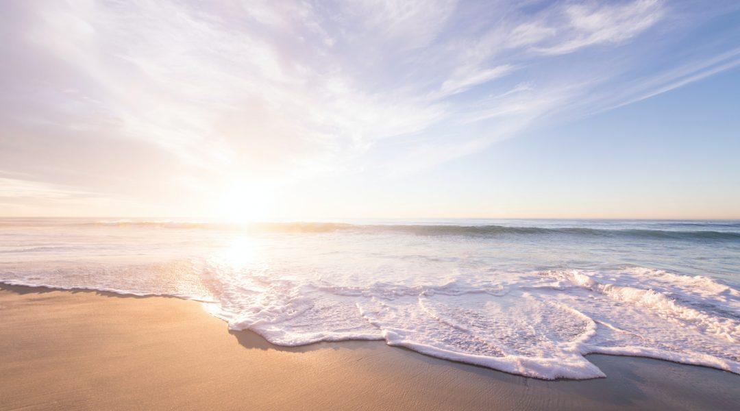Gentle waves breaking on a sandy beach.
