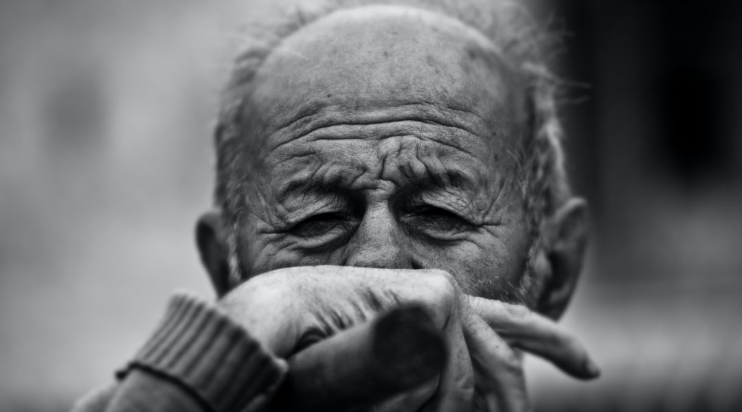 Elderly man with his hand covering his mouth in obvious discomfort.