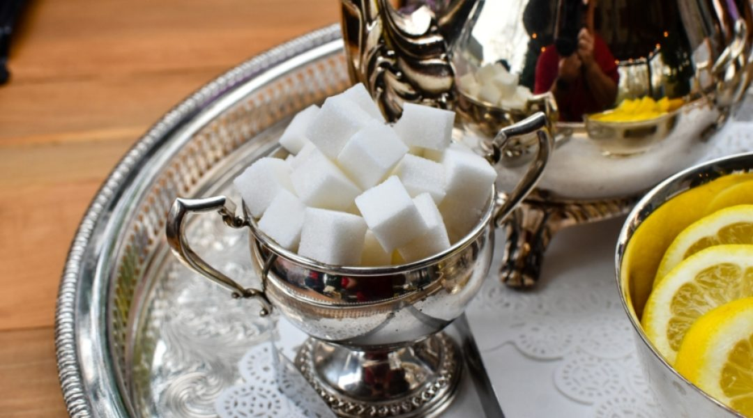 Sugar cubes in a silver bowl next to a tea pot and lemons
