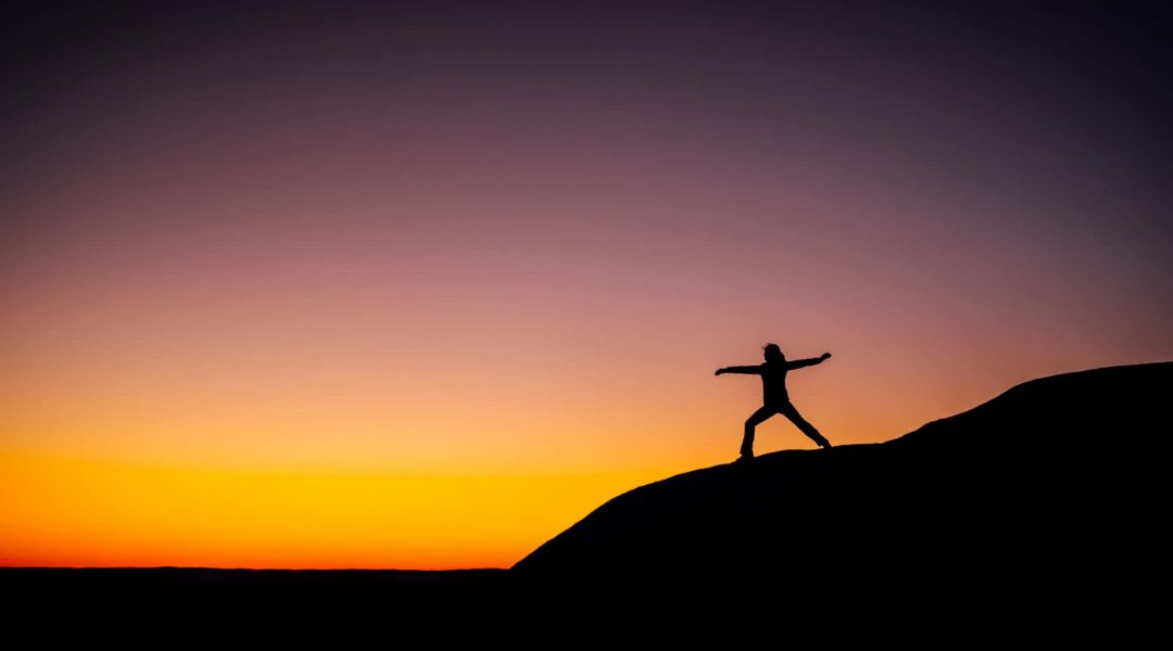 Woman doing yoga on a hill at sunset.