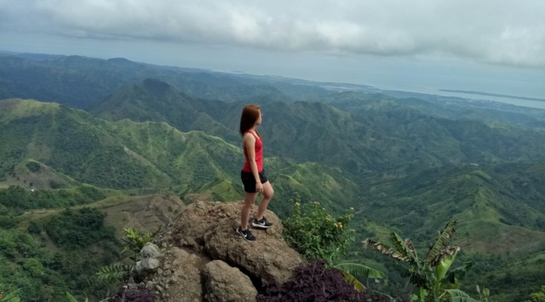 Woman standing on a rock outcropping overlooking a lush valley.